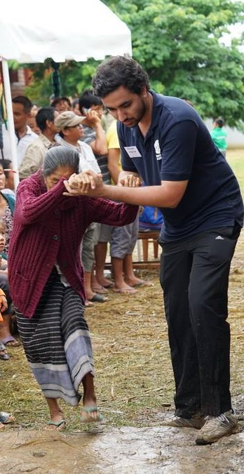 4)A student helping an elderly to walk across the mud after a rainy day.